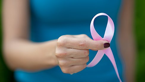 Hand holding pink ribbon symbolizing breast cancer