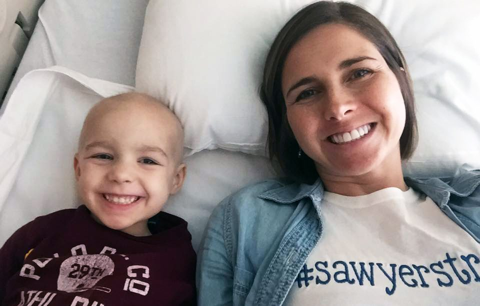 Pediatric cancer caregiver Amanda Hack next to her son, Sawyer, during his cancer treatment
