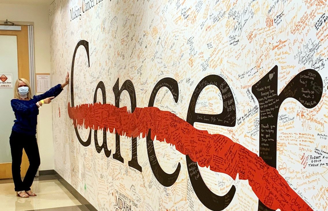 Squamous cell carcinoma survivor Jill Spencer points at the cancer strikethrough wall at the Proton Therapy Center after completing treatment