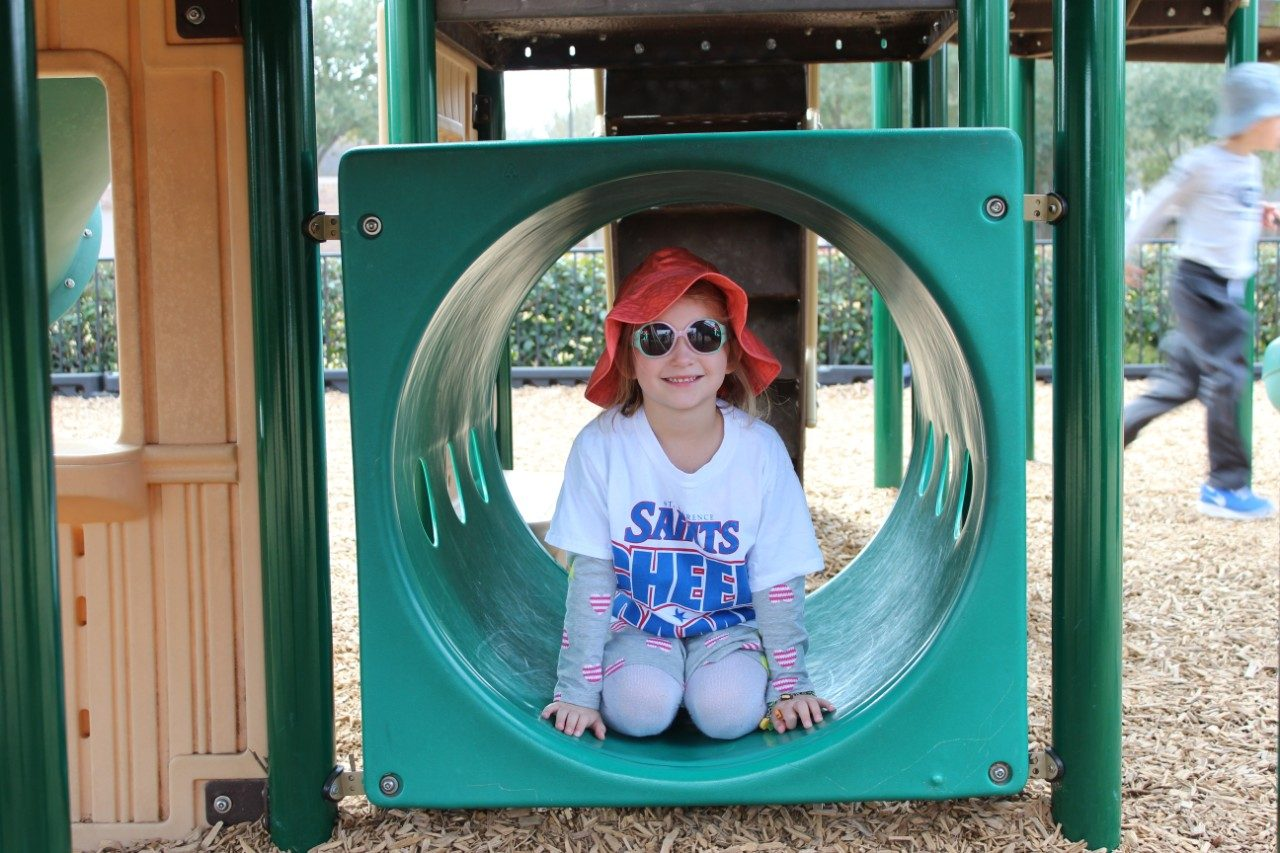 child on the playground in a hat