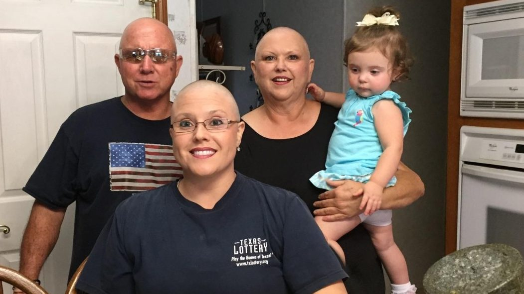 Breast cancer survivor Racheal Martin shows off her bald head with her family