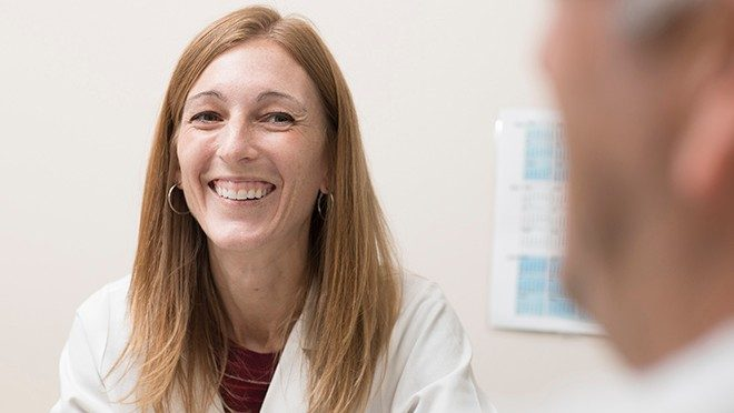 Courtney DiNardo, M.D., speaks with a patient