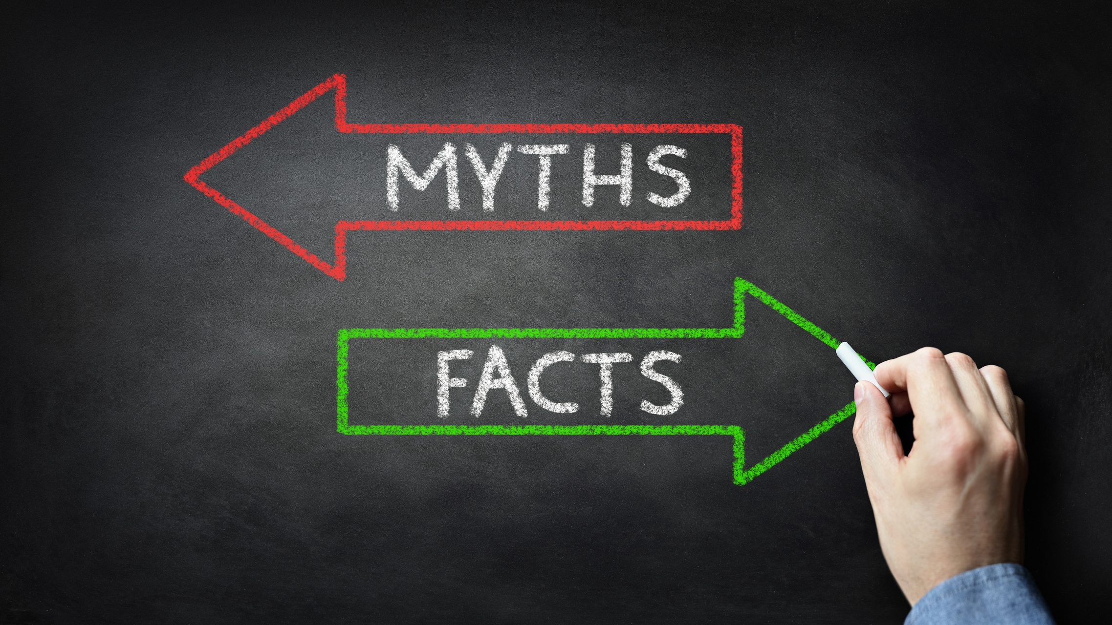 "Blackboard with the words ""myths"" and ""facts"" written inside red and green arrows"