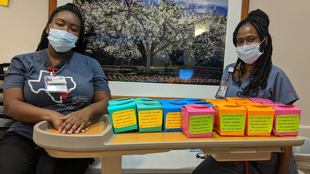 Patient care technician Tequicha Price (right) and patient services coordinator Ashley Stacey stand beside the inspiration boxes they made for patients.