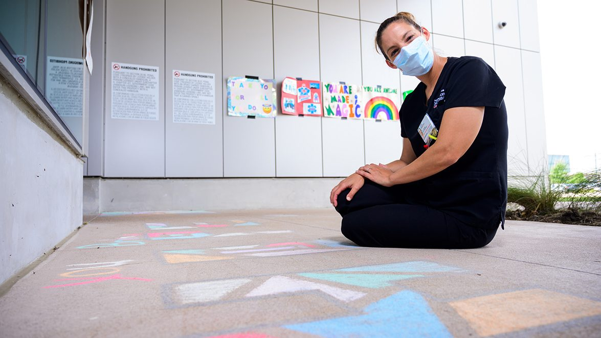 MD Anderson West Houston nurse manager Natalie Sanchez sits on the ground beside chalk art she and her team created for cancer patients