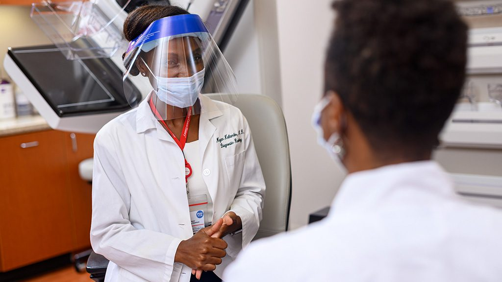 Timothy Yap, M.D., speaks with a patient while wearing a mask