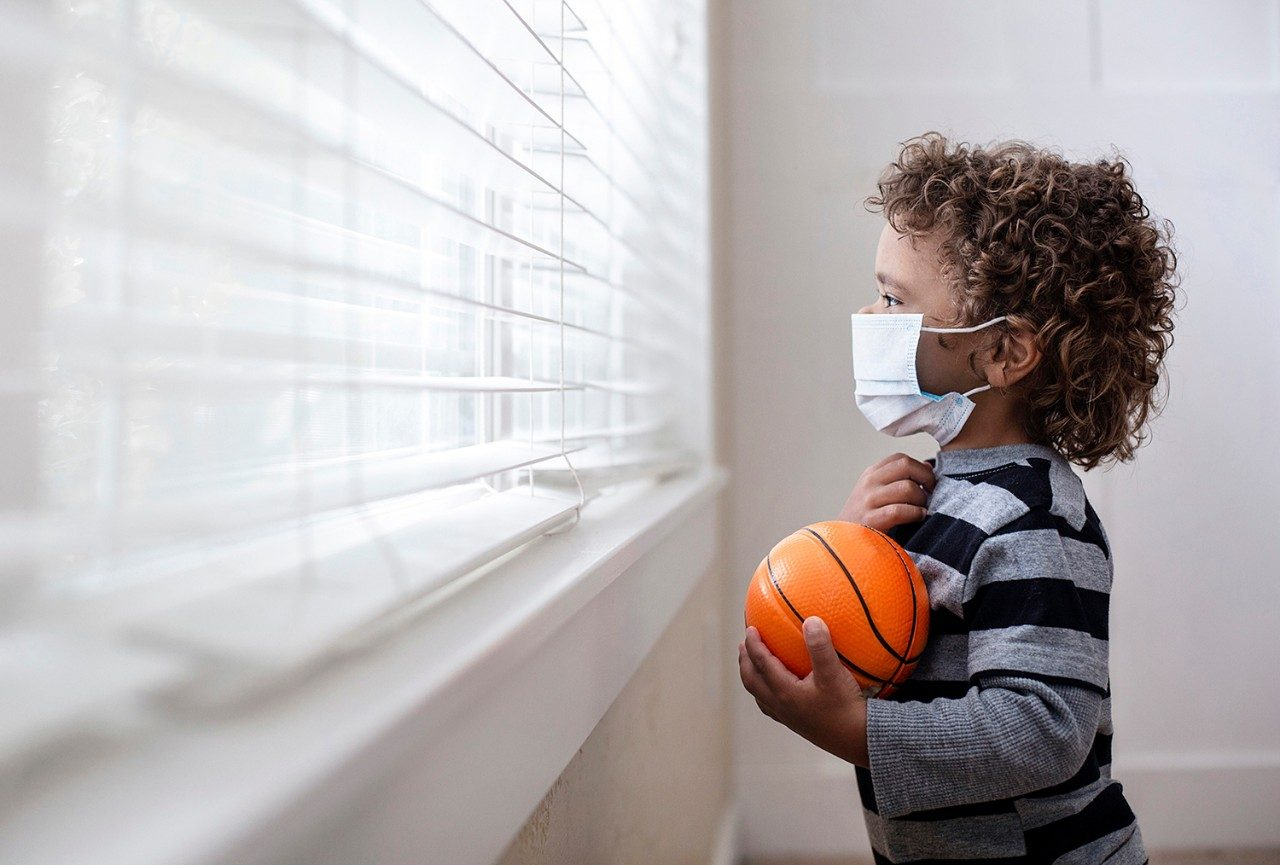 Toddler in mask holding basketball and looking out the window