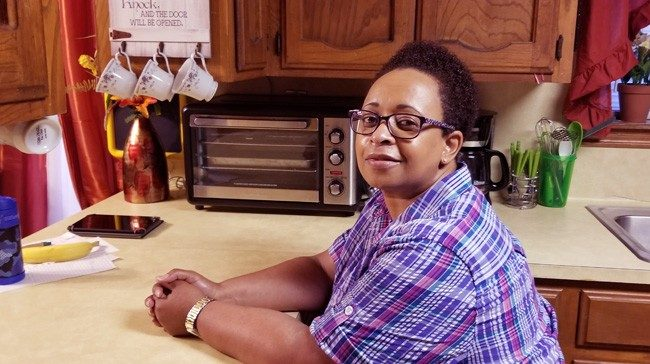 Trena Robertson sitting at her kitchen counter