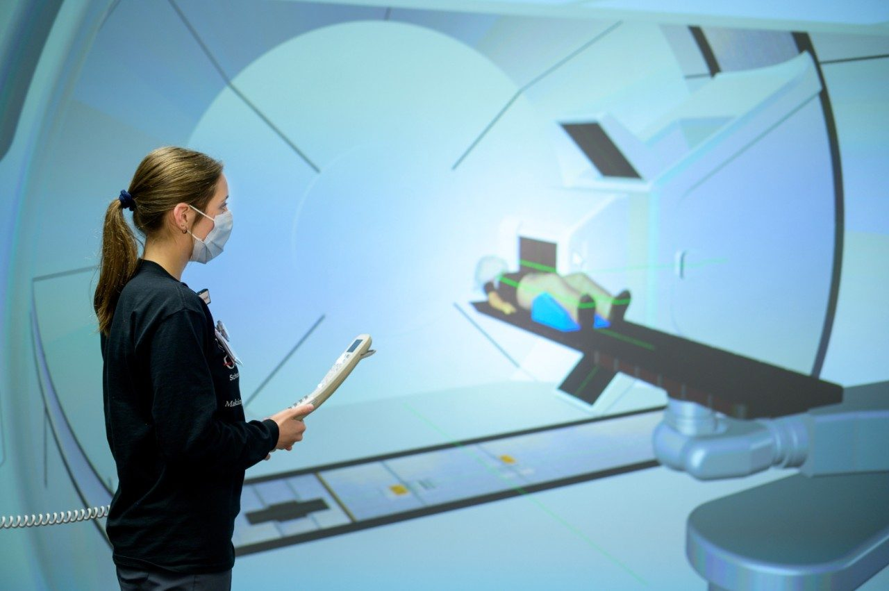 Radiation therapy student Jenna Casper practices delivering proton therapy to a simulated patient.