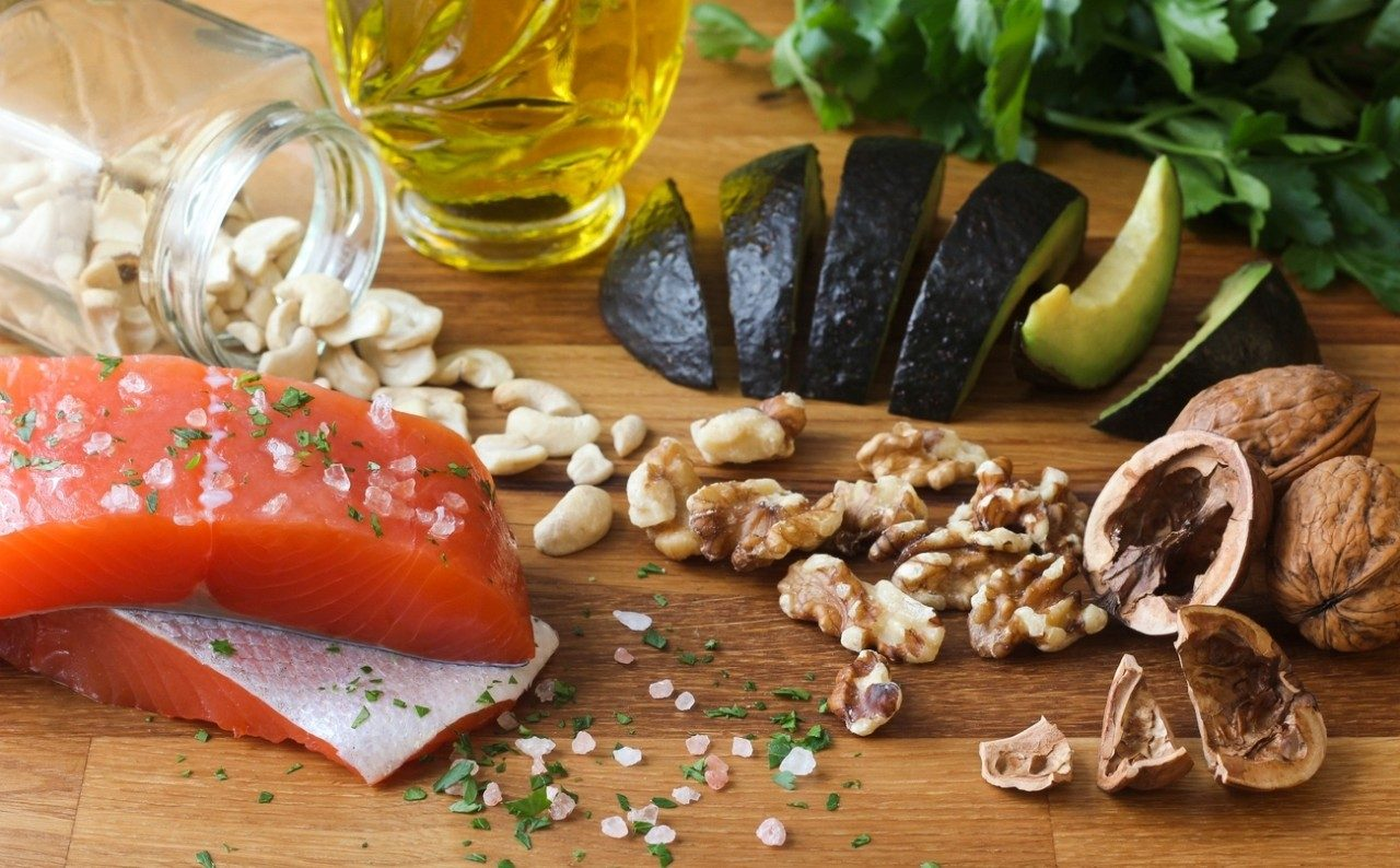 Some ingredients found in teh Meditteranean diet are shown on a board: salmon, walnuts, olive oil and avocado.