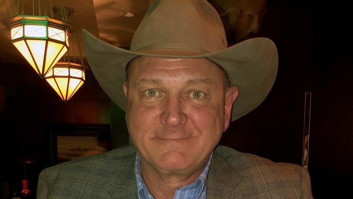 Tonsil cancer survivor Tony Loth poses in a cowboy hat
