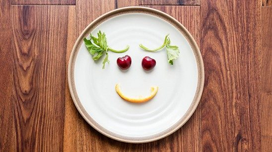 Plate with fresh food positioned to create a smiling face