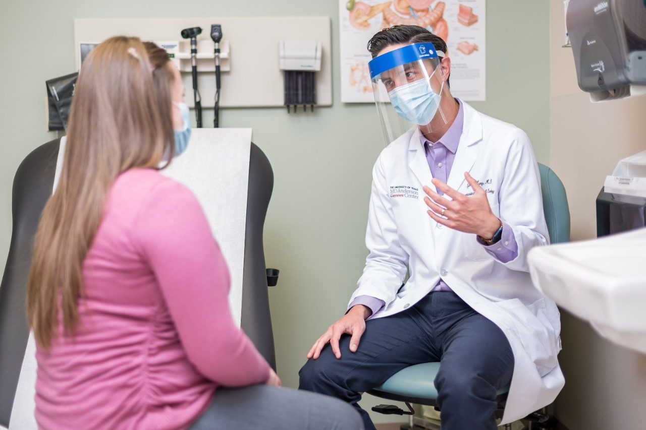 Ryan Huey, M.D., speaks with a patient while wearing a face shield over a medical-grade face mask.