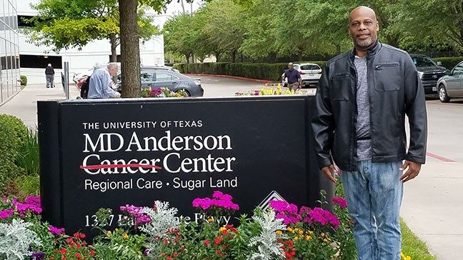 Pancreatic cancer survivor Drew Huggins standing beside MD Anderson in Sugar Land sign