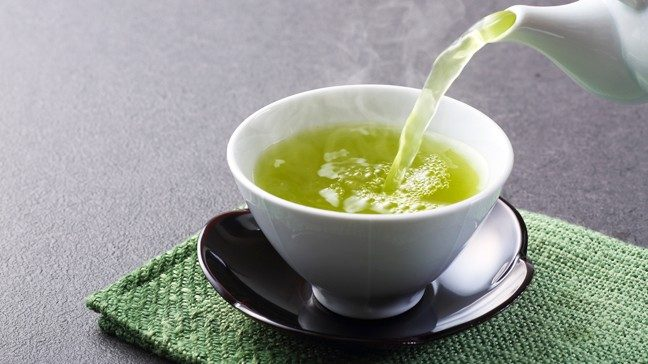 Green tea is shown being poured into a tea cup.