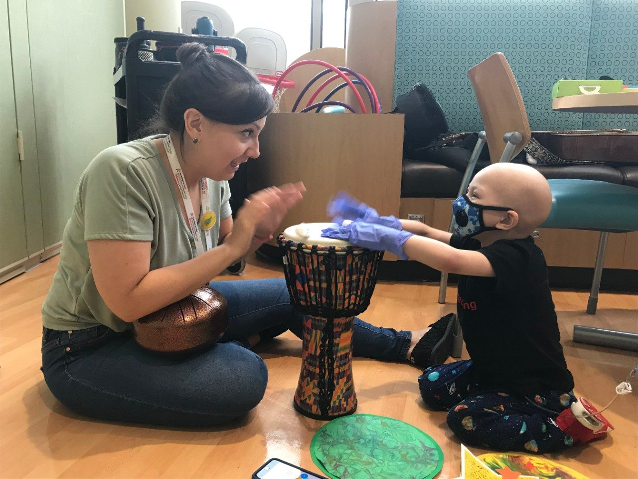Lady plays drum with pediatric patient