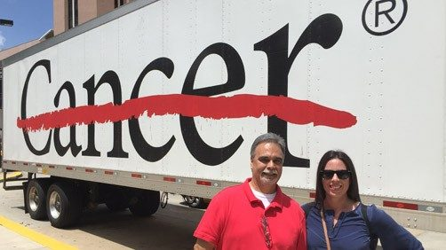 Audie Luna and her father standing in front of MD Anderson's cancer strikethrough logo on an 18-wheeler