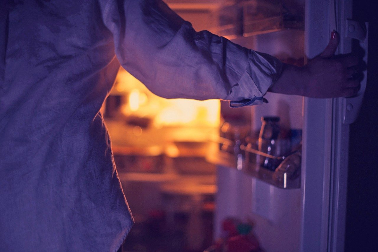 Person standing in front of open refrigerator in dark
