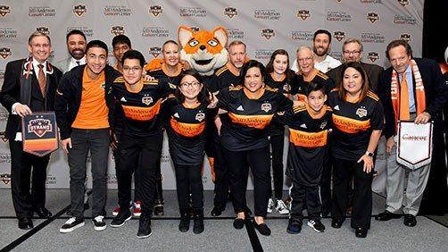 Houston Dynamo players and owners with MD Anderson President Peter Pisters