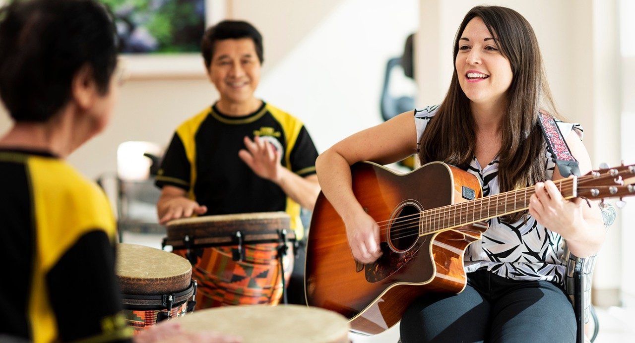Music therapist Sarah Folsom playing guitar with patients