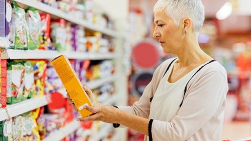 Woman looking at nutritional label on box