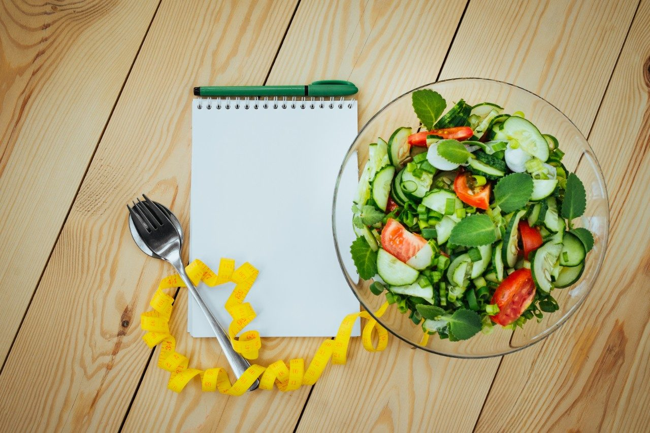 Salad next to a pad of paper and a pen