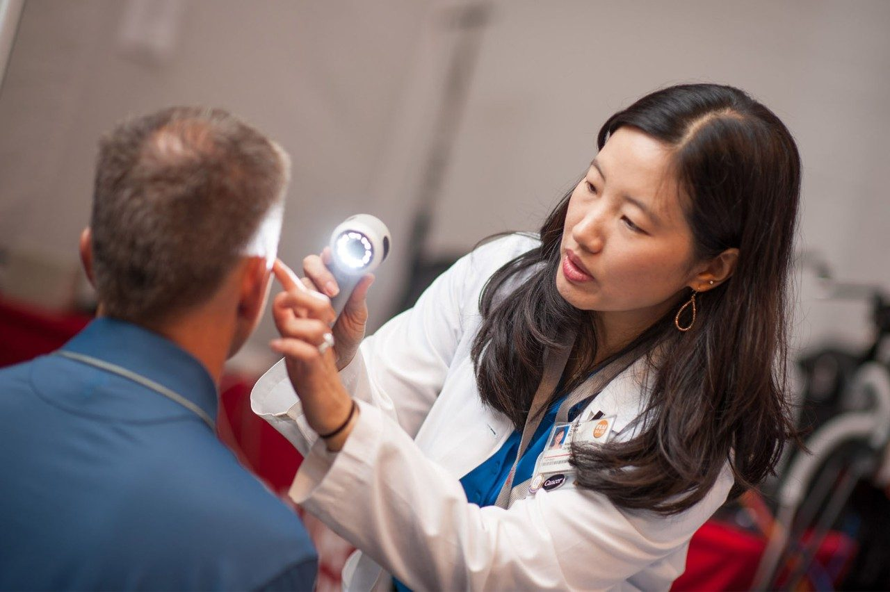 Doctor examining patient during skin cancer screening