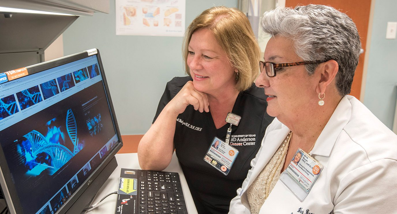 Wendy Brouwer, a women's health nurse practitioner in Clinical Cancer Prevention, reviews genetic information with nurse manager Carol Stalzer.