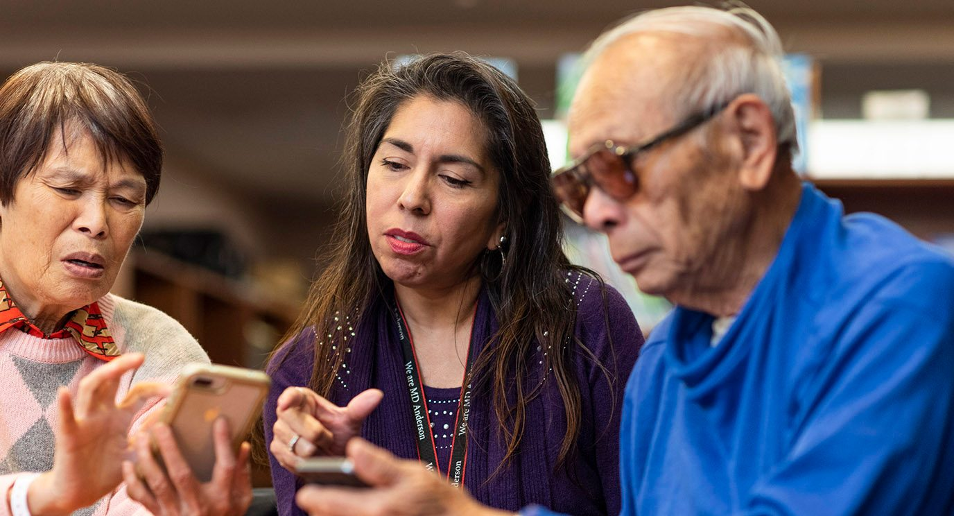 Librarian Adela Justice helps Barbara Hsu and her husband, Michael, download mobile apps.