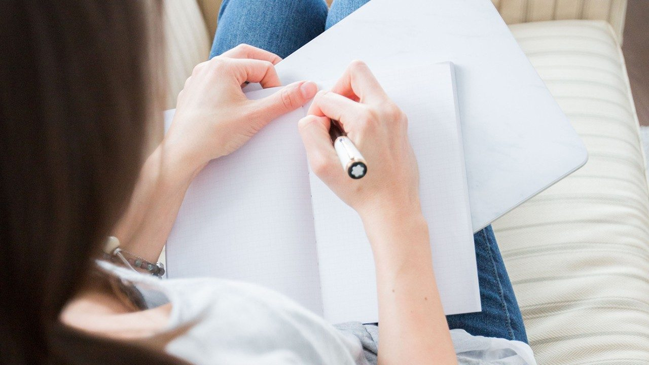 generic photo of woman writing in journal
