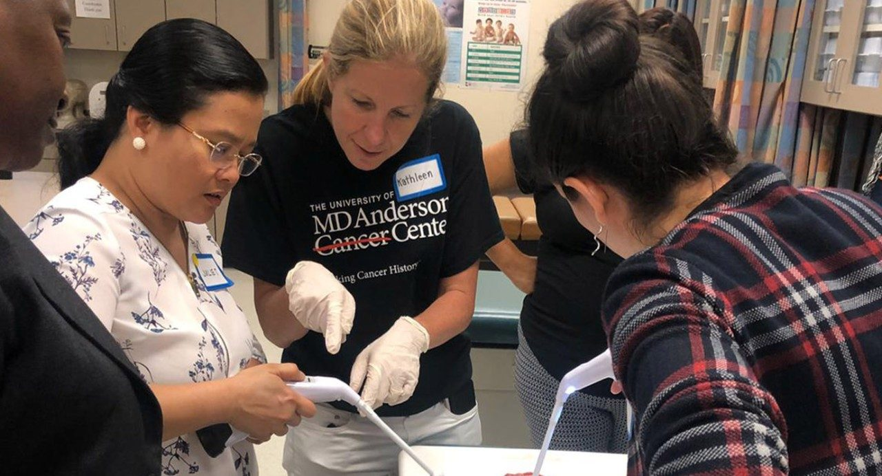 Kathleen Schmeler, M.D., teaching thermoablation to medical providers at a cervical cancer prevention training course in Tyler, Texas. Thermoablation applies heat to remove precancerous growths detected during cervical cancer screening.