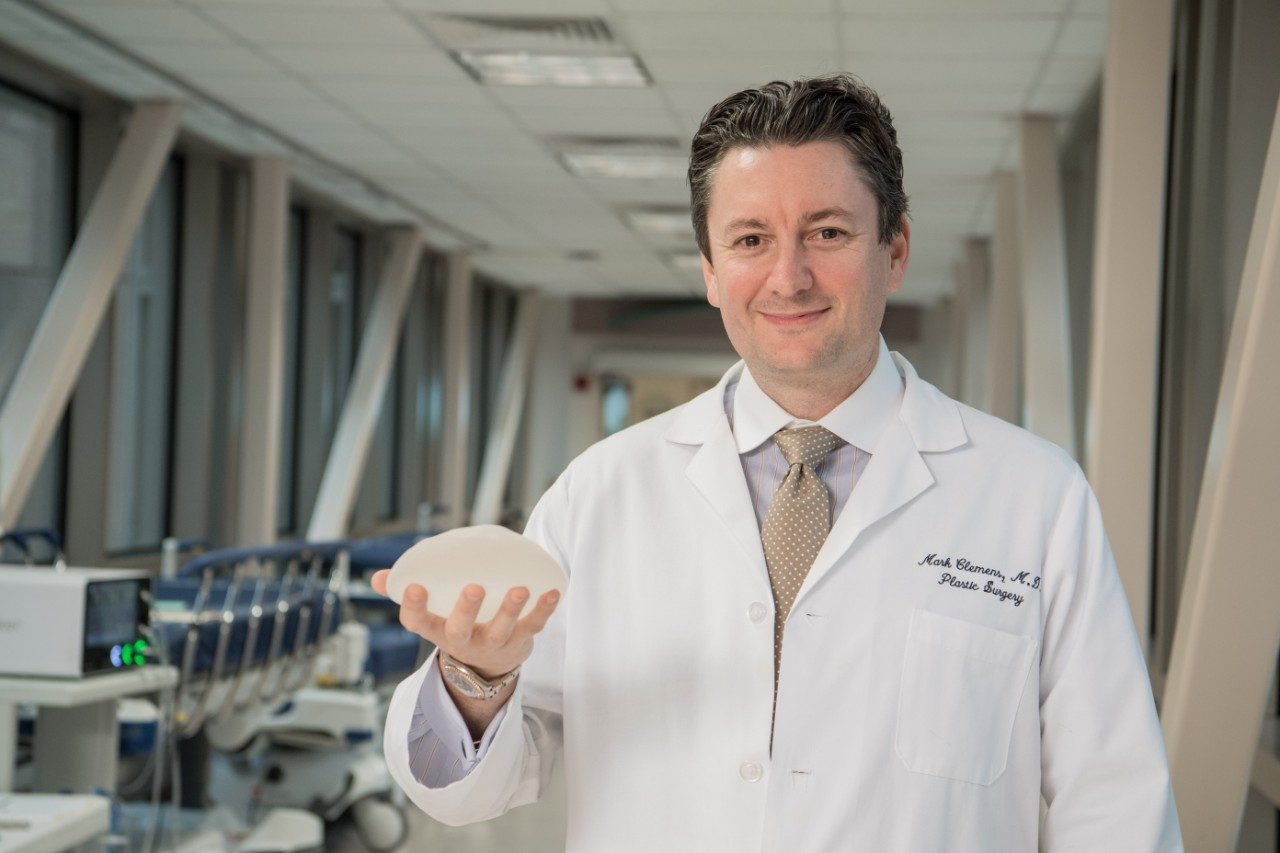 Breast implant-associated anaplastic large cell lymphoma expert Mark Clemens, M.D., holds a textured breast implant.