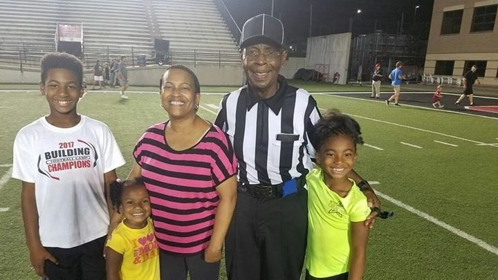 Kidney cancer survivor Primus Moore poses in his referee uniform with his family on a football field