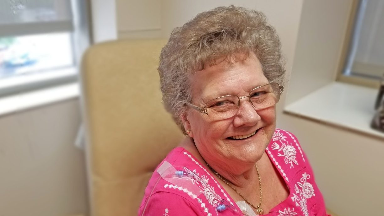Colorectal cancer survivor June Graham smiles as she receives maintenance chemotherapy