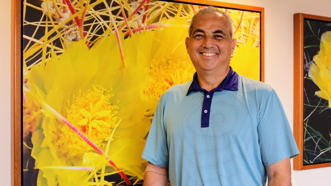Glioblastoma survivor Tino Gonzalez poses by artwork at MD Anderson