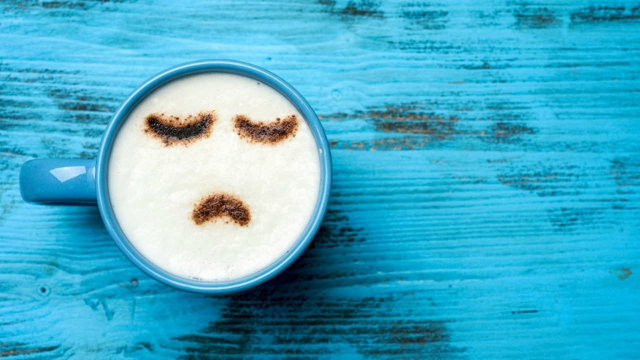 Coffee mug with sad face to depict depression