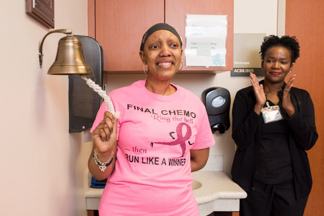 Triple-negative breast cancer survivor and MD Anderson employee Uniqua Smith, Ph.D., rings the bell to mark the end of her chemotherapy treatment