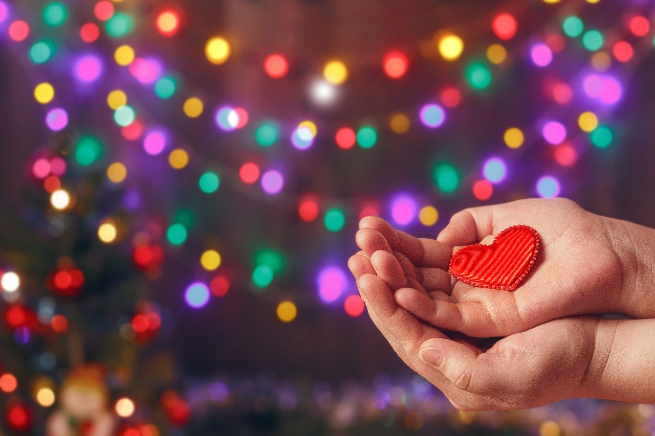 Hands holding a felt heart by holiday lights