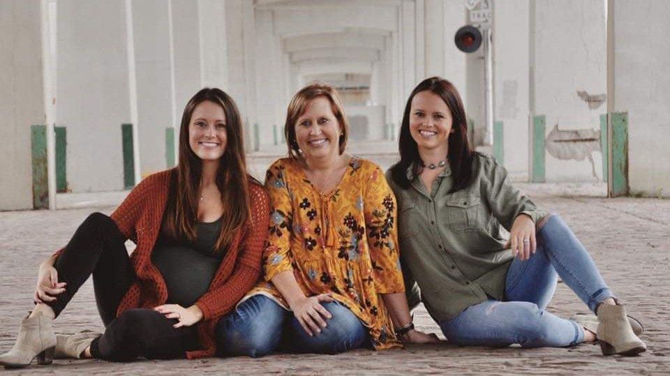Inflammatory breast cancer survivor Tiffany Honken poses with her two daughters