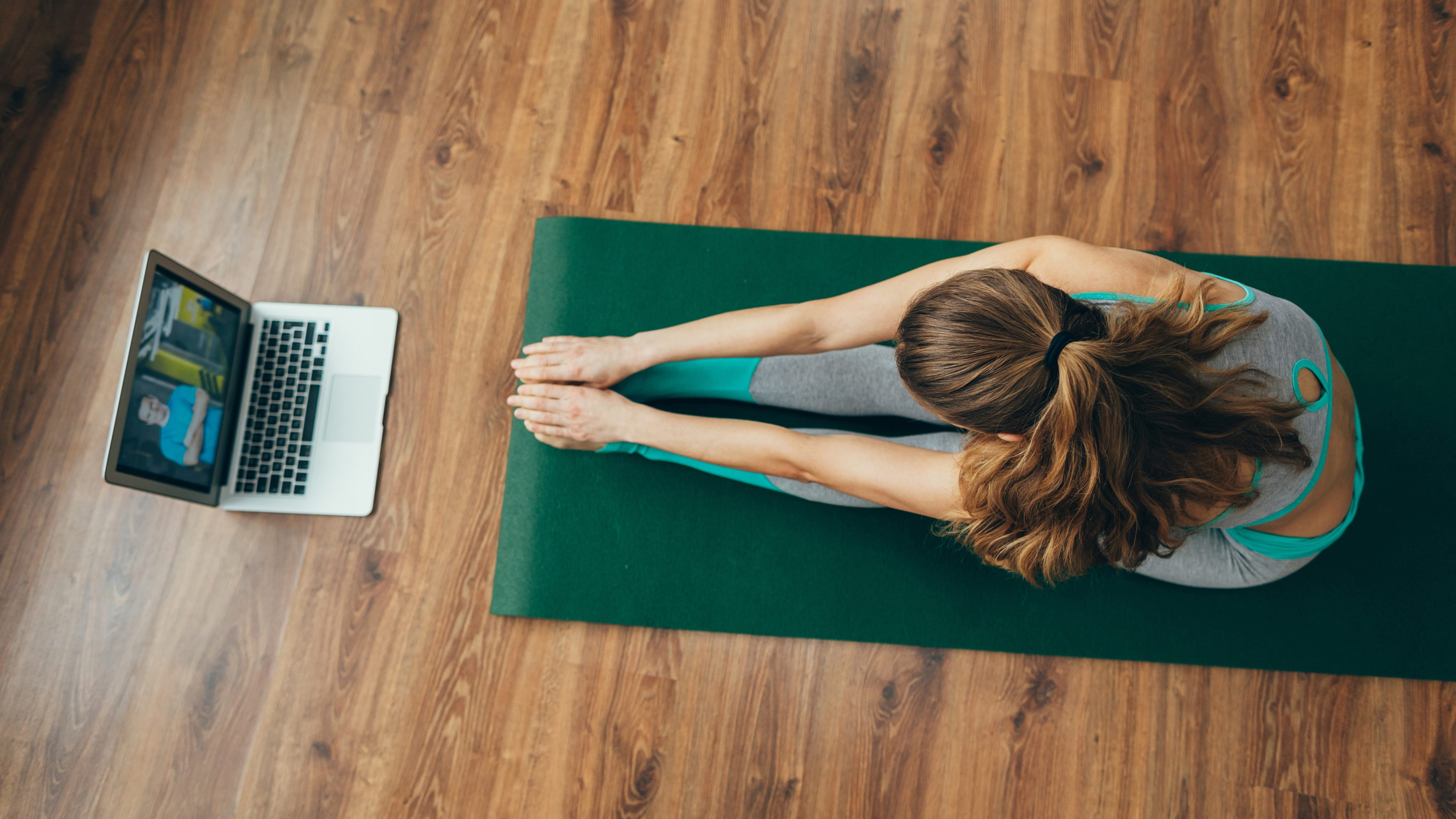 Woman doing yoga at home while looking at computer screen