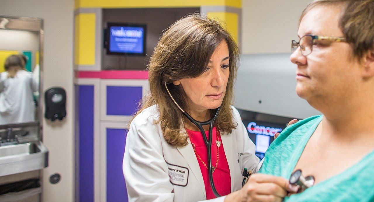 Najat Daw, M.D., uses a stethoscope to listen to a patient's lungs.