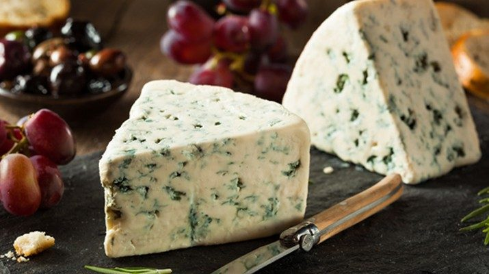 Two blocks of blue cheese on a chopping board
