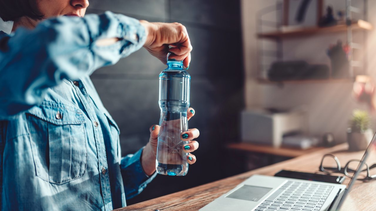Woman at desk opens bottle of water