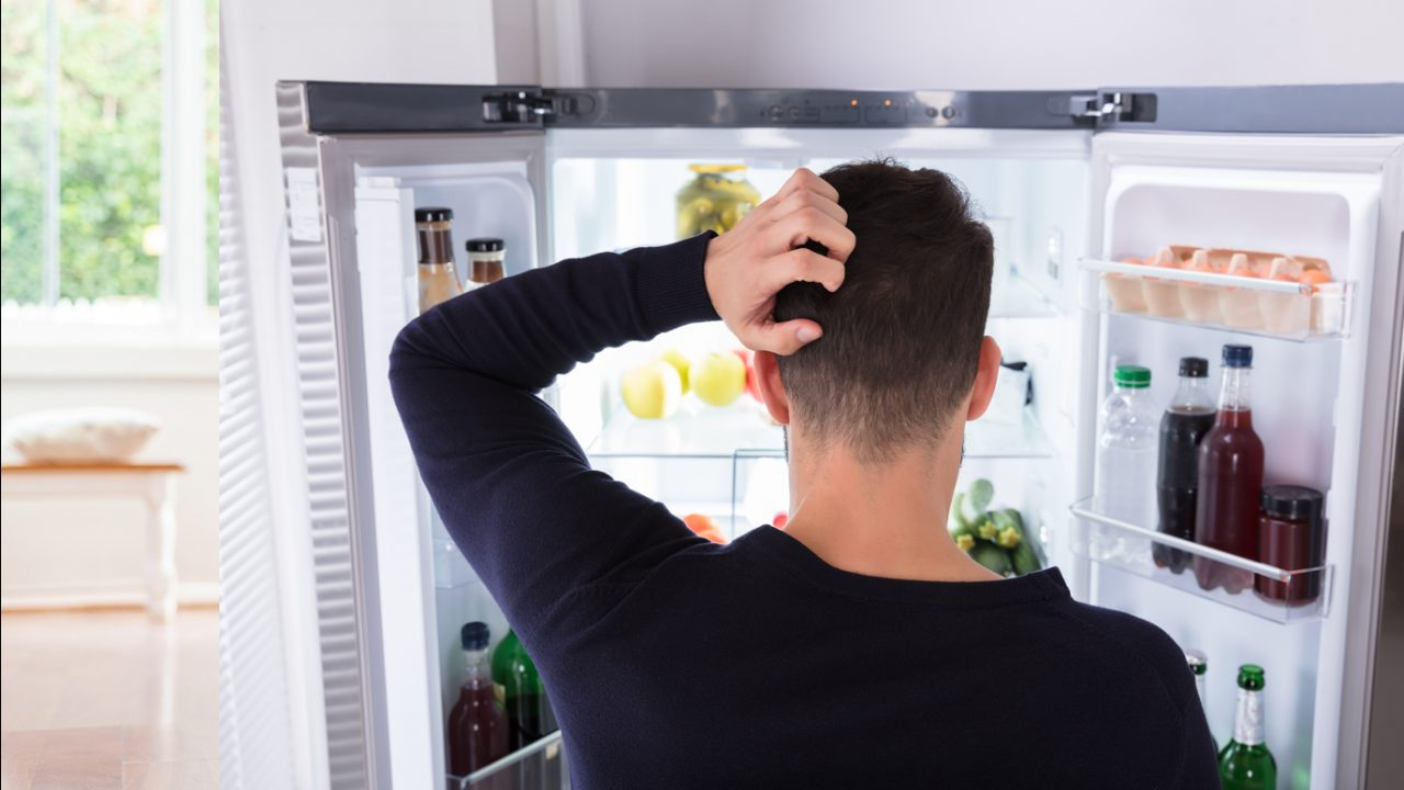 Man looks in fridge and scratches head