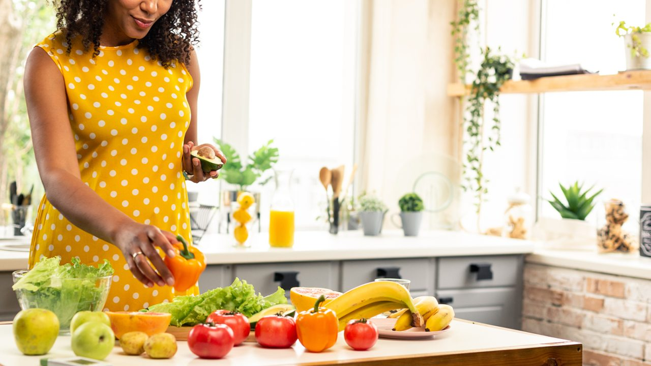 Woman prepares healthy meal at kitchen work station