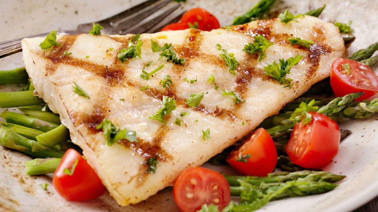 Grilled filet of white fish on plate with tomatoes and asparagus.