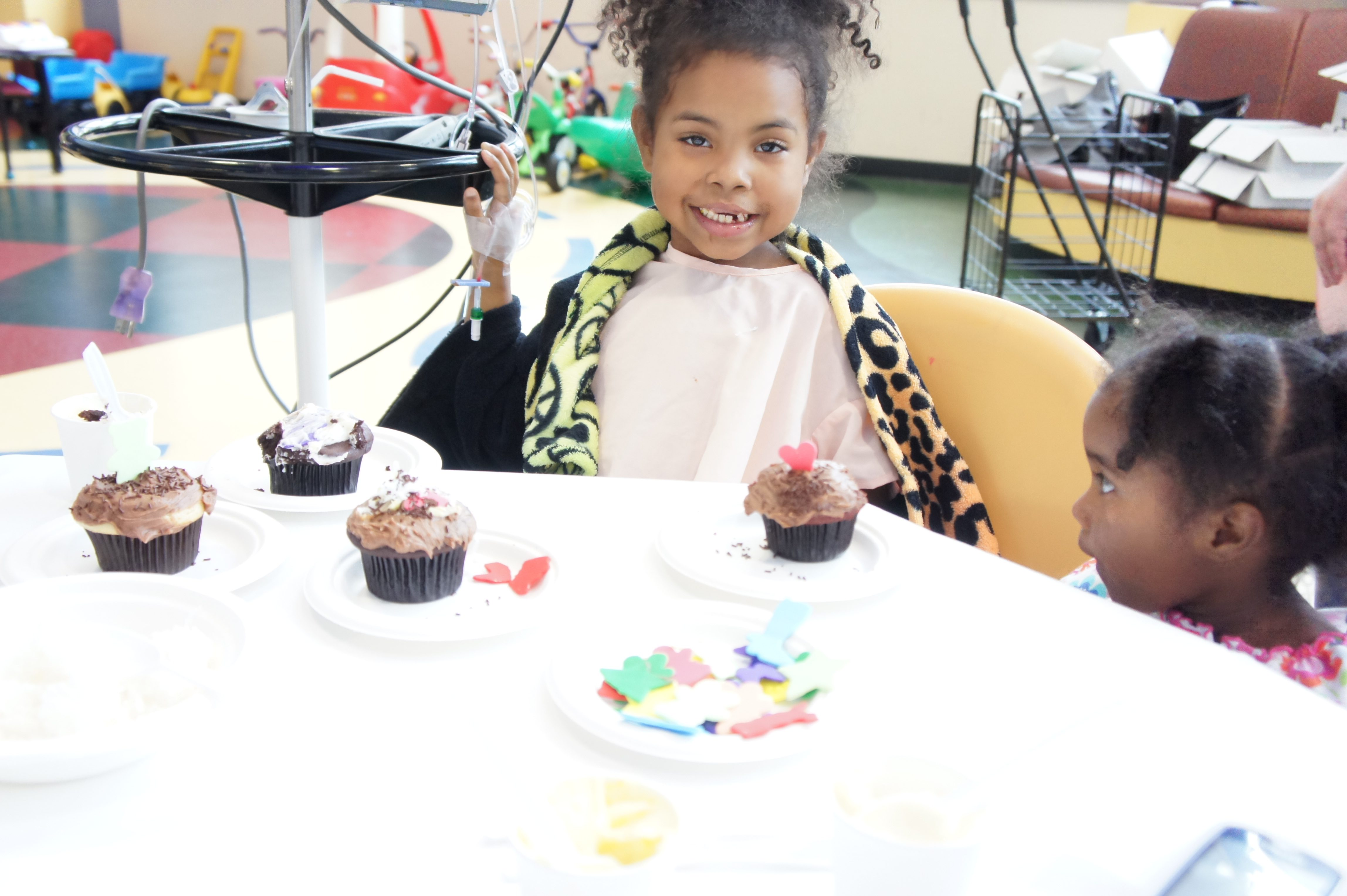 Jakaya Crawfod, a patient at MD Anderson Children's Cancer Hospital, prepares to enjoy a piece of edible art as her sister looks on at the recent party celebrating Crave Cupcakes' partnership with Arts in Medicine. Photo by Ian Cion.