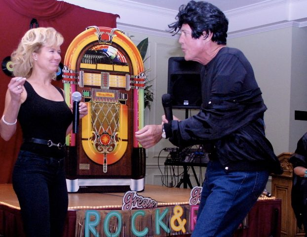 "AudubonCARES co-chairs Joyce Sauer, left, and Bill Weidenfeller channel ""Grease"" as they sing and dance at the neighborhood talent show, Audubon's Got Talent. Photo courtesy of AudubonCARES."