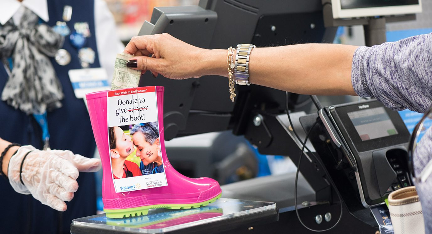 A Walmart associate holds a pink rain boot used to collect donations at her register.