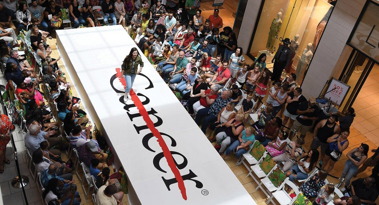 Young model struts on runway featuring MD Anderson Cancer Center logo.